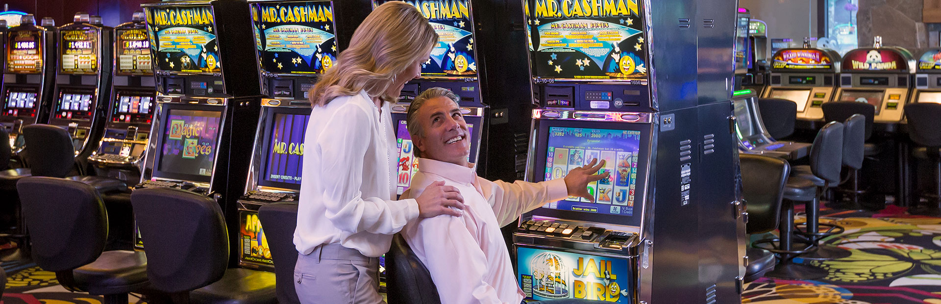 Man and woman enjoying playing slots